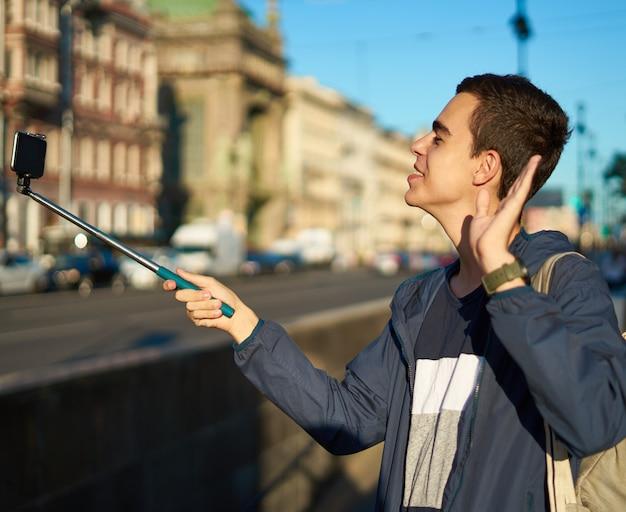 Młody człowiek z telefonem jest na ulicy dużego miasta i macha ręką