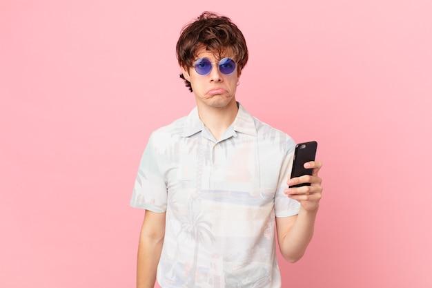 Młody człowiek z telefonem komórkowym czuje się smutny i jęczy z nieszczęśliwym spojrzeniem i płaczem