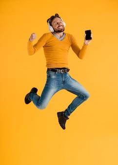 Młody człowiek z telefonem komórkowym i słuchawkami skaczącymi