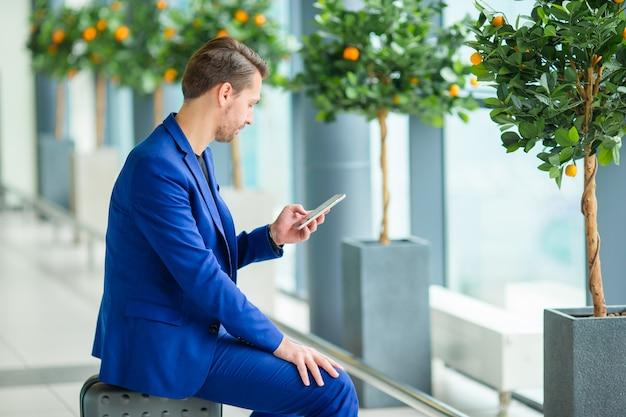 Młody człowiek z telefonem komórkowym na lotnisku podczas oczekiwania na wejście na pokład.