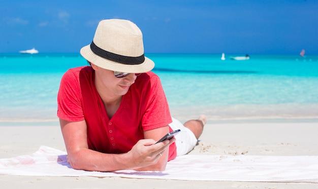 Młody człowiek z telefonem komórkowym na tropikalnej biel plaży