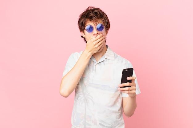 Młody człowiek z telefonem komórkowym obejmujące usta rękami z szoku
