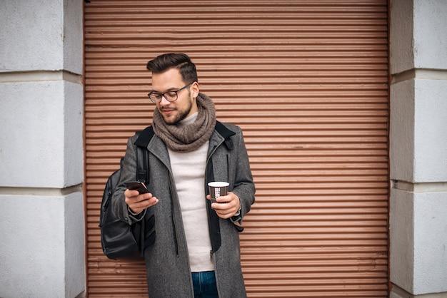 Młody człowiek z telefonem komórkowym w jego ręce, pije kawę outdoors w mieście.