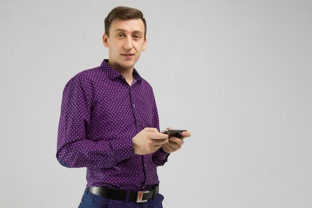 Młody człowiek z telefonem komórkowym w jego rękach odizolowywa na świetle