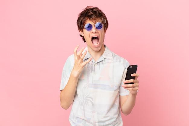 Młody człowiek z telefonem komórkowym wygląda na zdesperowanego sfrustrowanego i zestresowanego