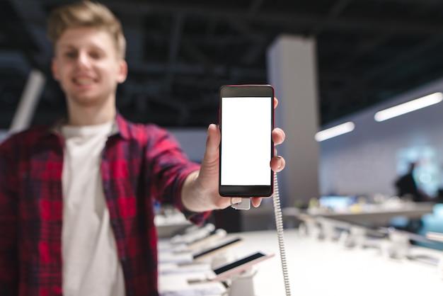 Młody człowiek z telefonem w rękach sklep elektroniczny.