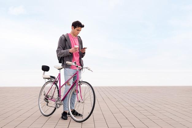 Młody człowiek z telefonem wyglądającym na rower i kawę