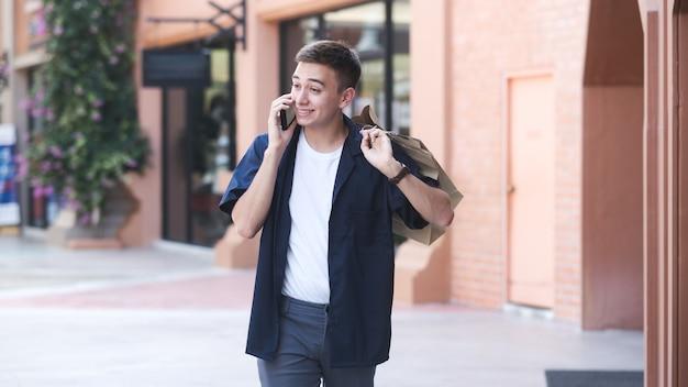Młody człowiek z torby na zakupy korzysta z telefonu komórkowego podczas robienia zakupów
