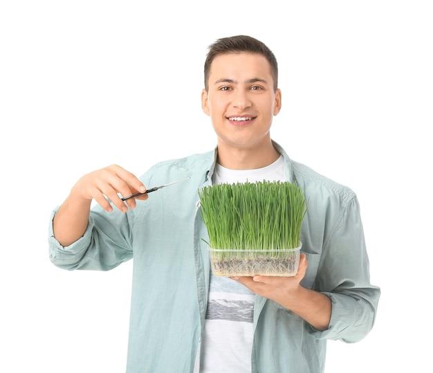Młody człowiek z trawą pszeniczną na białym