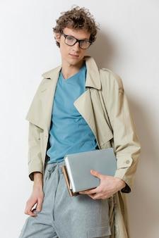 Młody człowiek z trenczem w okularach i trzymając książki