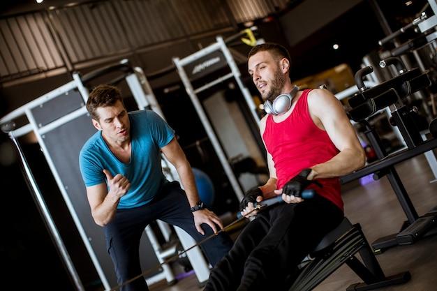 Młody człowiek z trenerem robi ćwiczenia na siłowni