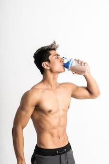 Młody człowiek z umięśnionym ciałem, trzymając butelkę i pić jedną ręką stanąć twarzą do boku
