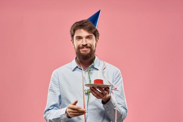 Młody człowiek z uroczystym tortem z plastrami obchodzi jedno urodziny w czapce, izolacji i kwarantannie