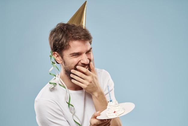 Młody człowiek z uroczystym tortem z plastrami obchodzi jedno urodziny w czapce