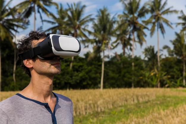 Młody człowiek z vr szkłami w tropikalnym ryżu polu