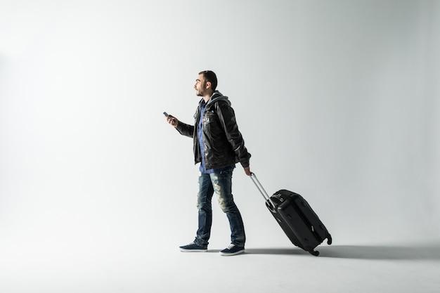 Młody człowiek z walizką podróżną spaceru na białym tle nad białym tle