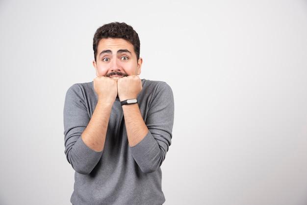 Młody człowiek z wąsem przestraszony wkładając ręce do ust.
