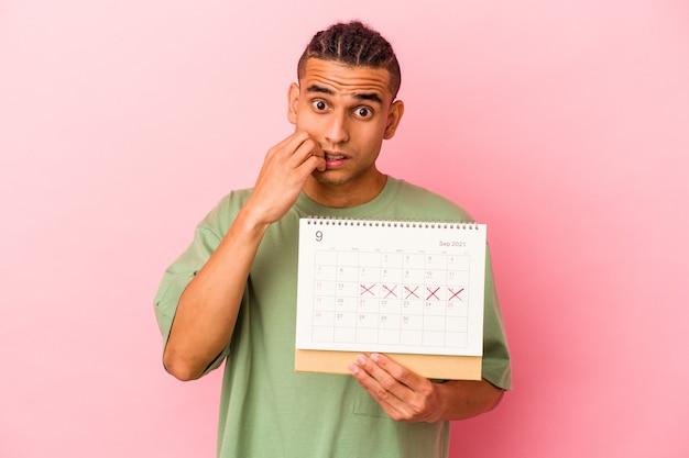 Młody człowiek z wenezueli trzymający kalendarz na białym tle na różowym tle gryzie paznokcie, nerwowy i bardzo niespokojny.