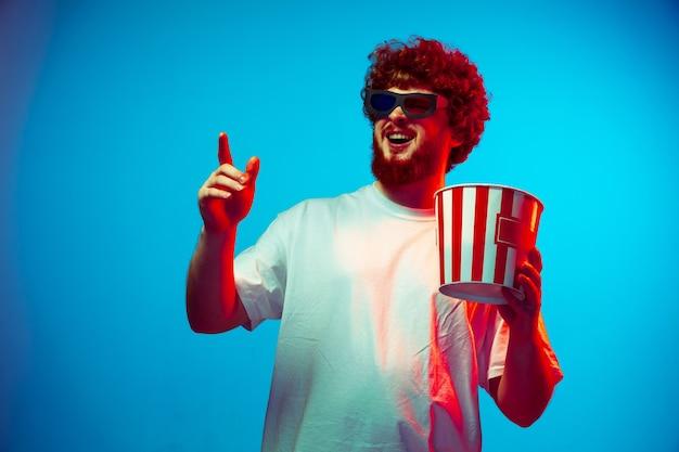 Młody człowiek z wiadrem popcornu w kinie