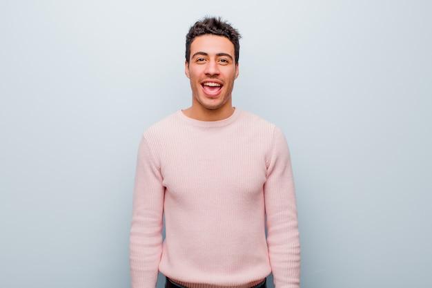 Młody człowiek z wielkim, przyjaznym, beztroskim uśmiechem, wyglądający pozytywnie, zrelaksowany i szczęśliwy, relaksujący nad szarą ścianą