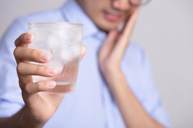 Młody człowiek z wrażliwymi zębami i ręka trzyma szklankę zimnej wody z lodem
