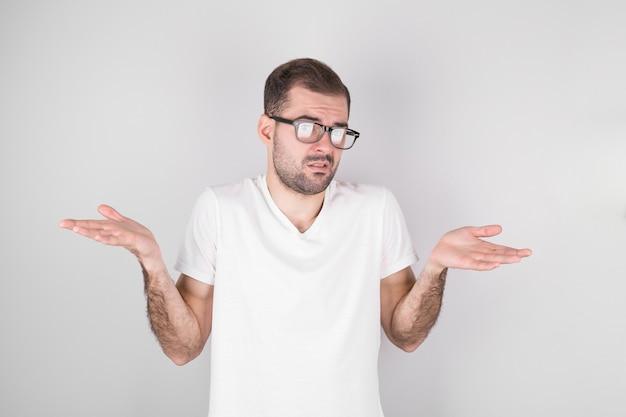 Młody człowiek z wyciągniętymi ramionami, wzruszając ramionami, mówi: nie wiem. na białym tle na szarym tle.