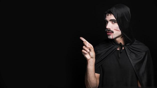 Młody człowiek z zadrapaniami malował na bladej twarzy pozuje w halloweenowym kostiumu