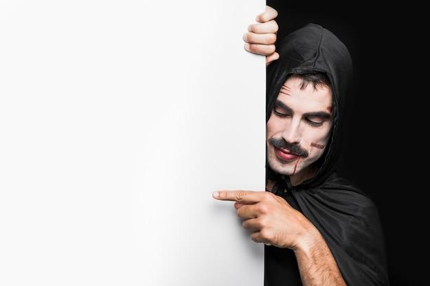 Młody człowiek z zadrapaniami na twarzy w czarnej pelerynie z kapiszonem pozuje w studiu