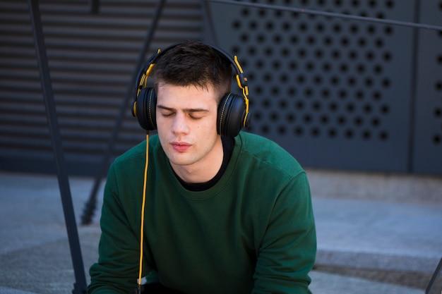 Młody człowiek z zamkniętymi oczami słuchając muzyki w słuchawkach