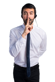 Młody człowiek z zestawu słuchawkowego co gest ciszy