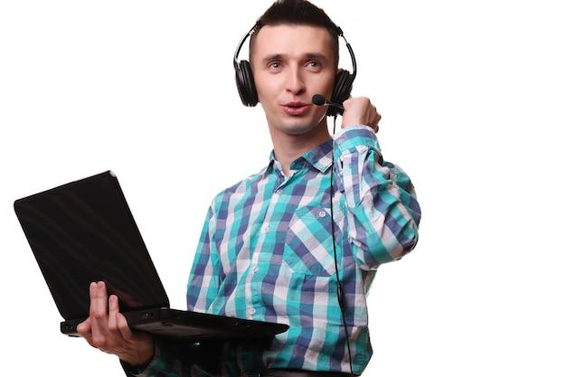 Młody człowiek z zestawu słuchawkowego posiadania laptopa - centrum telefoniczne człowiek z zestawu słuchawkowego i laptopa na białej ścianie