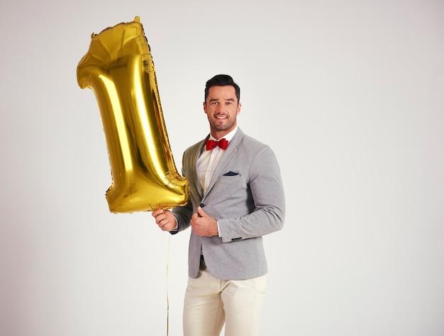 Młody człowiek z złotym balonem świętuje pierwsze urodziny swojej firmy