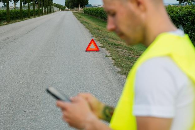 Młody człowiek z żółtą kamizelką odblaskową, nazywając swoją pomoc samochodu blisko jego uszkodzonego samochodu