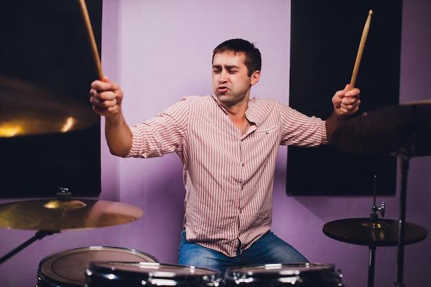 Młody człowiek za instalacją typu perkusyjnego w profesjonalnym studiu nagraniowym.
