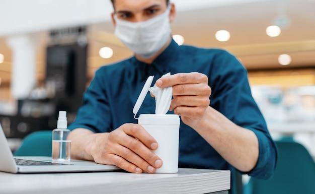 Młody człowiek za pomocą chusteczek antyseptycznych w miejscu pracy