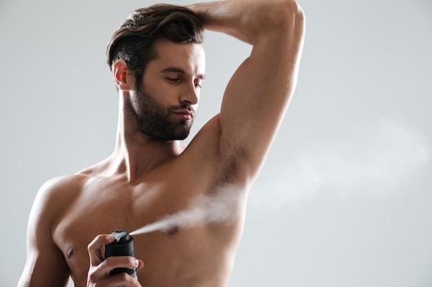 Młody człowiek za pomocą dezodorantu