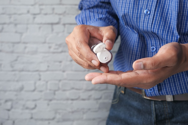 Młody człowiek za pomocą dezynfekcji rąk do zapobiegania wirusom