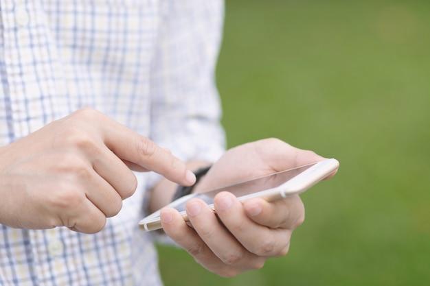 Młody człowiek za pomocą inteligentnego telefonu komórkowego.