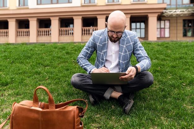Młody człowiek za pomocą laptopa na zewnątrz niezależny student technologii edukacji stylu życia i koncepcji zakupów online
