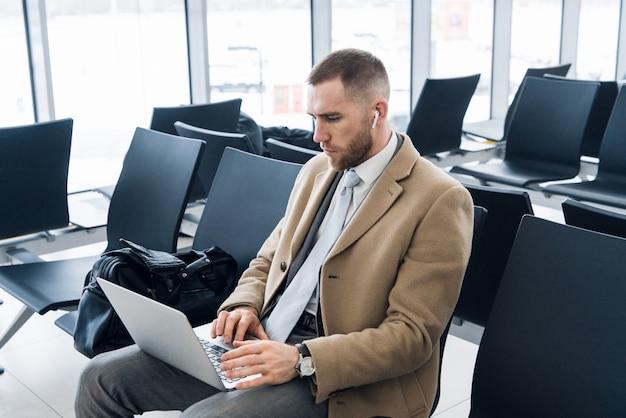 Młody człowiek za pomocą laptopa w terminalu lotniska