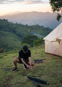 Młody człowiek za pomocą młotka, rozbijanie namiotu na kemping na łące