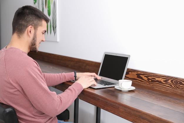 Młody człowiek za pomocą nowoczesnego laptopa w kawiarni