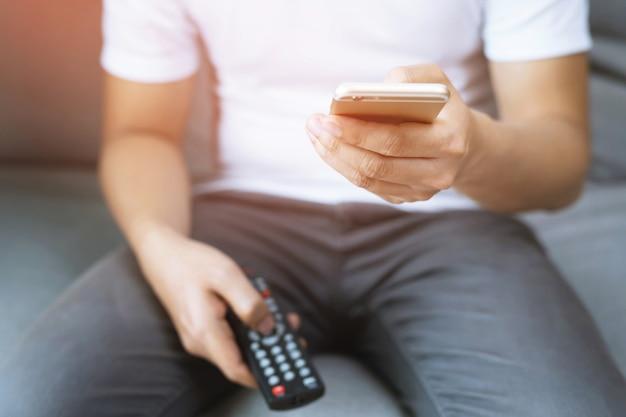 Młody człowiek za pomocą pilota do telewizora i inteligentny telefon komórkowy siedzi na kanapie