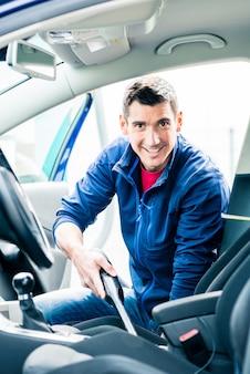 Młody człowiek za pomocą próżni do czyszczenia wnętrza samochodu