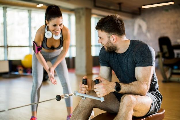 Młody człowiek za pomocą siedzącej maszyny rzędu w siłowni ze wsparciem trenera kobiet