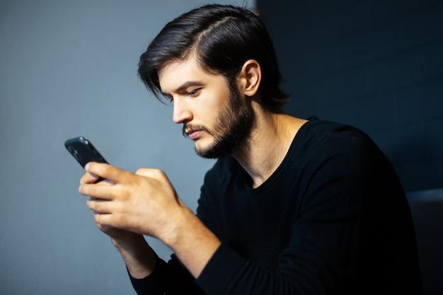Młody człowiek za pomocą smartfona na tle szarej i czarnej ściany.