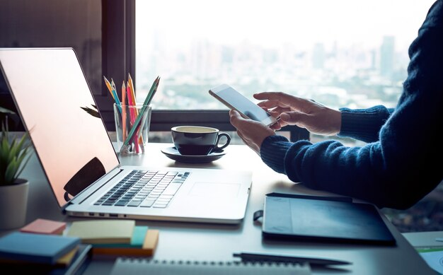 Młody człowiek za pomocą smartfona z nowoczesnym stołem roboczym i laptopem