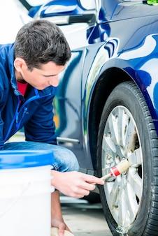 Młody człowiek za pomocą szczotki do czyszczenia powierzchni obręczy niebieskiego samochodu w myjni automatycznej