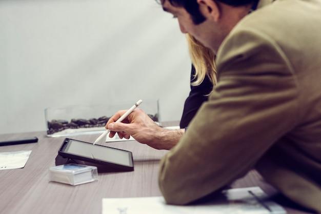 Młody człowiek za pomocą tabletu w biurze spotkania z partnerami biznesowymi