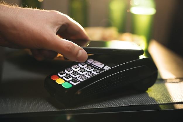 Młody człowiek za pomocą technologii nfc portfela bezgotówkowego smartfona, aby zapłacić za zamówienie w sieci bezprzewodowej
